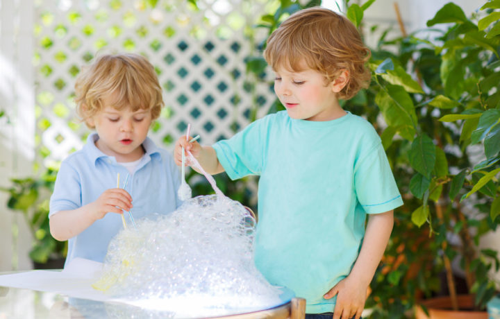 Two cute friend boys making experiment with colorful bubbles